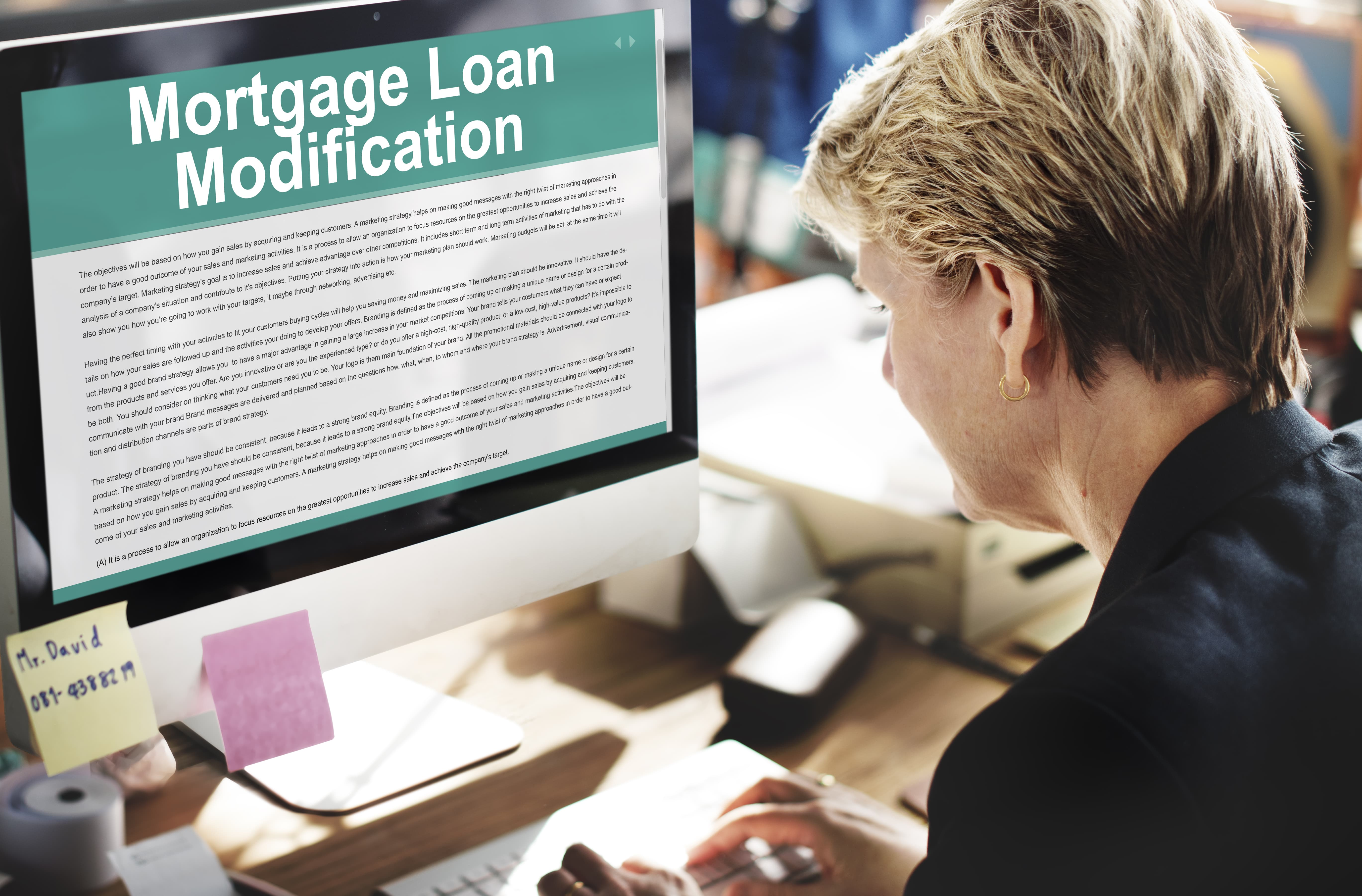 Woman watching on her monitor the mortgage loan modification form.