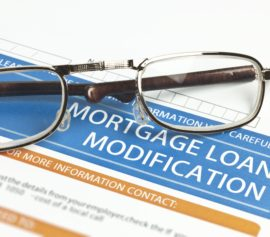 Mortgage loan modification form with eyeglasses on top.
