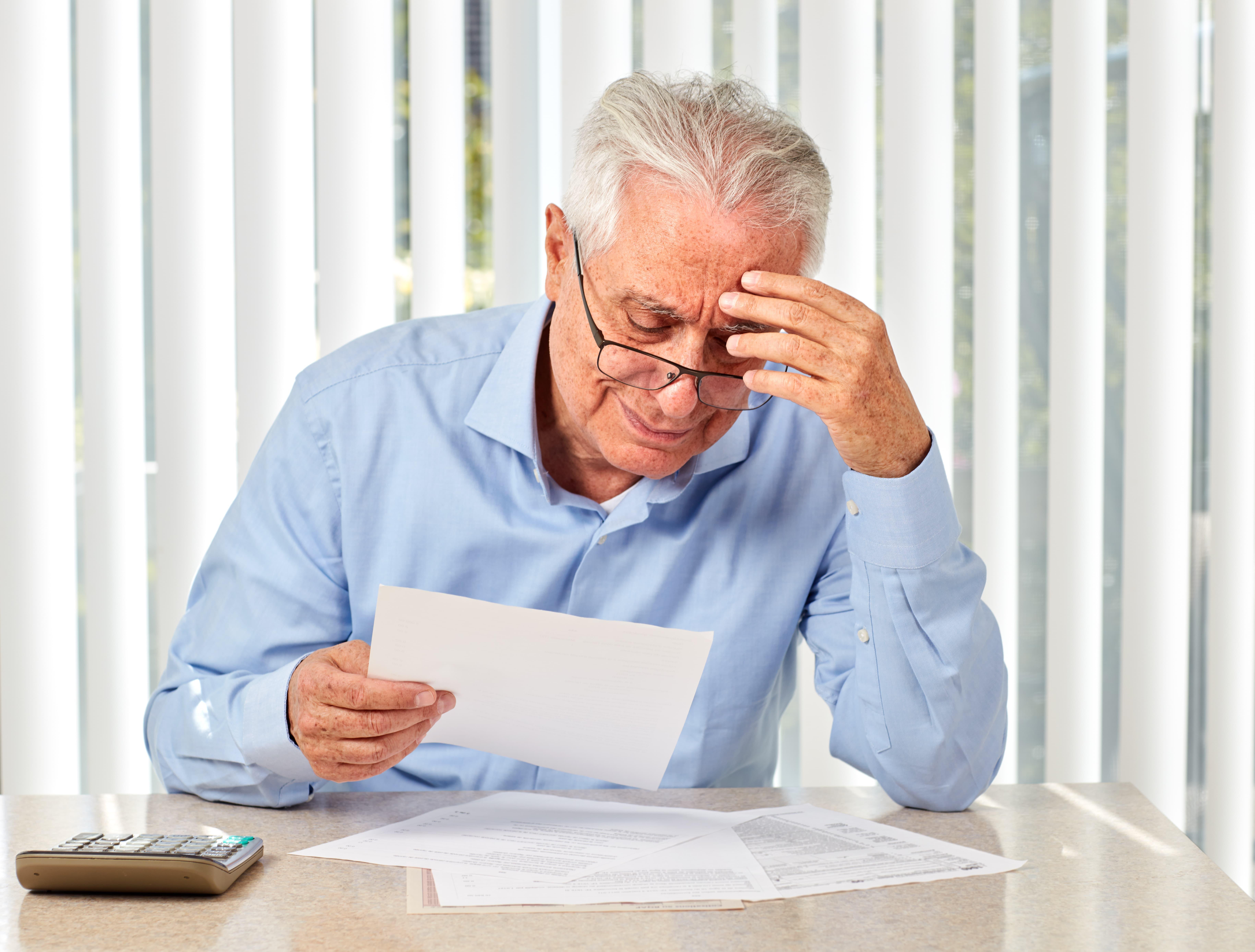 Sad old man filing for bankruptcy.