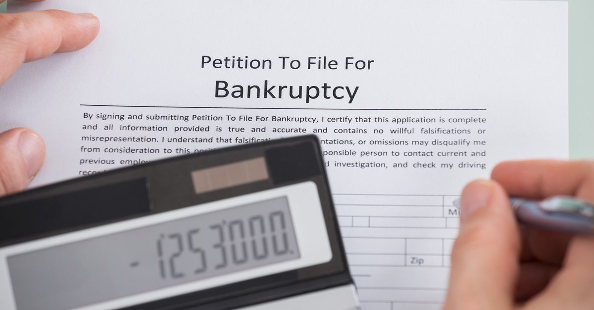 Businessman writing a petition to file for bankruptcy.
